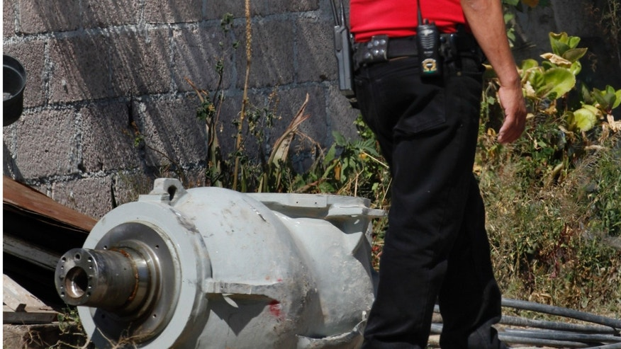 Dec. 5, 2013 - A firefighter stands next to the radiation head that was part of a radiation therapy machine, in the patio of the family who found the abandoned radiation head in a nearby field in the village of Hueypoxtla, Mexico. Officials were engaged Thursday in the delicate task of recovering the stolen shipment of highly radioactive cobalt-60 abandoned in a rural field in central Mexico state. According to National Commission of Nuclear Safety and Safeguards, the radioactive source had been removed from the radiation head and was found nearby in an empty lot.