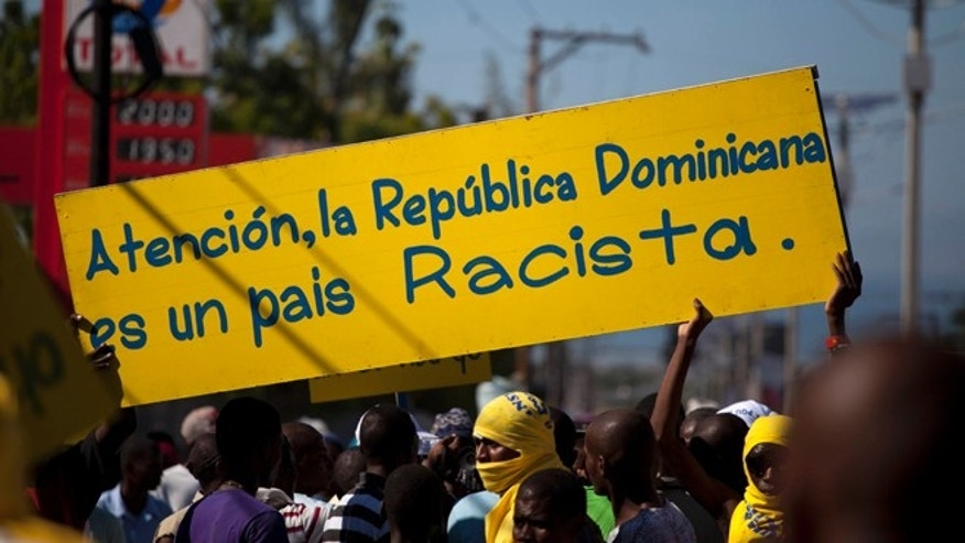 "Protesters hold a banner that reads in Spanish; ""Attention, the Dominican Republic is a racist country,"" in Port-au-Prince, Haiti, Friday, Dec. 6, 2013. Hundreds of people gathered near the Dominica Embassy decrying a recent court decision in the Dominican Republic that could strip the citizenship of generations of people of Haitian descent living in the neighboring country. (AP Photo/Dieu Nalio Chery)"