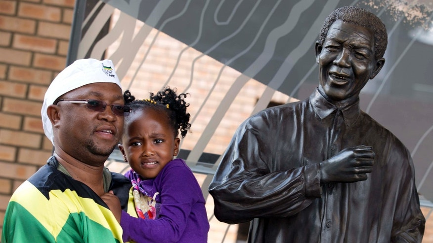 A man draped in the South African flag holds his daughter as he poses for a picture with a statue of Nelson Mandela at the Nelson Mandela Centre of Memory in Johannesburg, South Africa, Saturday Dec. 7, 2013. Flags were lowered to half-staff and people in black townships, in upscale mostly white suburbs and in South Africa's vast rural grasslands commemorated Nelson Mandela with song, tears and prayers on Friday while pledging to adhere to the values of unity and democracy that he embodied. (AP Photo/Peter Dejong)