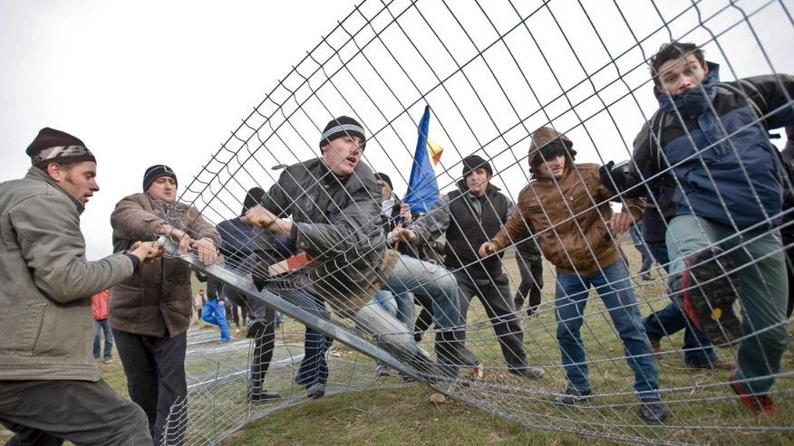 Anti-shale gas exploration protesters bring down a fence in Pungesti, north eastern Romania, Saturday, Dec. 7, 2013. Hundreds of villagers destroyed the fences around a plot of land owned by US energy company Chevron, during protests meant to stop shale gas exploration in the area. (AP Photo/Mircea Restea)