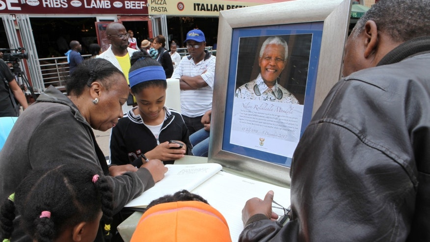 A family writes messages in a condolence book, next to a picture of former South African president, Nelson Mandela, in Sandton, Johannesburg, South Africa, Saturday, Dec. 7, 2013. South Africa is readying itself for the arrival of a flood of world leaders for the memorial service and funeral of Nelson Mandela as thousands of mourners continued to flock to sites around the country Saturday to pay homage to the freedom struggle icon. (AP Photo/Tsvangirayi Mukwazhi)