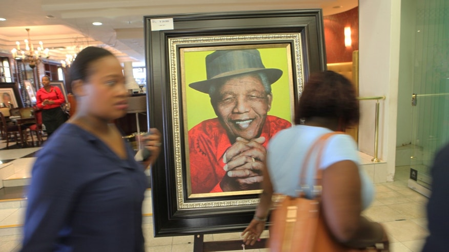 Women walk past art works of Nelson Mandela for sale in Sandton, Johannesburg, South Africa, Saturday, Dec. 7, 2013. South Africa is readying itself for the arrival of a flood of world leaders for the memorial service and funeral of Nelson Mandela as thousands of mourners continued to flock to sites around the country Saturday to pay homage to the freedom struggle icon. (AP Photo/Tsvangirayi Mukwazhi)