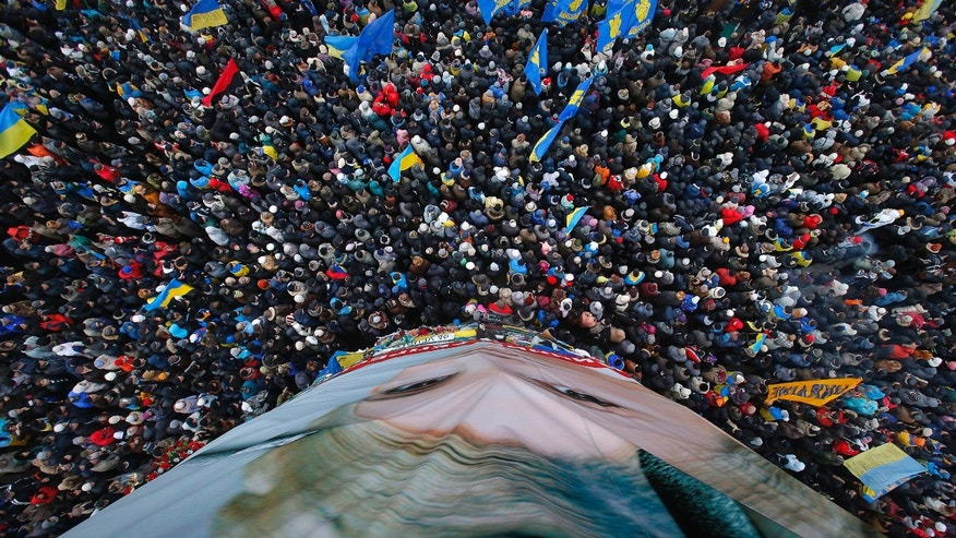 Pro-European Union activists gather around a huge poster of jailed former Ukrainian Prime Minister Yulia Tymoshenko, bottom, during a rally in the Independence Square in KIev, Ukraine, Sunday, Dec. 8, 2013. Over 200,000 angry Ukrainians occupied a central Kiev square on Sunday, to denounce President Viktor Yanukovych's decision to turn away from Europe and align this ex-Soviet republic with Russia, as massive protests continued for a third week. (AP Photo/Sergei Grits)