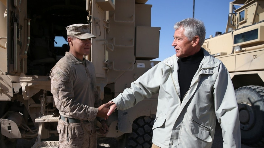 U.S. Secretary of Defense Chuck Hagel, right, shakes hands with U.S. Marine Lance CPL. Arron Corona as he works on a MRAP vehicle, at Camp Bastion, Afghanistan, Sunday, Dec. 8, 2013. Hagel spoke with troops and thanked them for being deployed for the holidays. (AP Photo/Mark Wilson, Pool)
