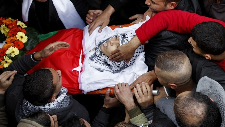 Palestinians carry the body of Wajeeh Ramahi, 15, during his funeral at the Jalazoun refugee camp near the West Bank city of Ramallah, Sunday, Dec. 8, 2013. Wajdi Ramahi from the Jalazoun refugee camp near Ramallah said his son, Wajeeh, was killed by a shot to the back on Saturday. The father said his son was shot from an Israeli army watchtower in the nearby Beit El settlement. The Israeli military says it is looking into the report. (AP Photo/Majdi Mohammed)