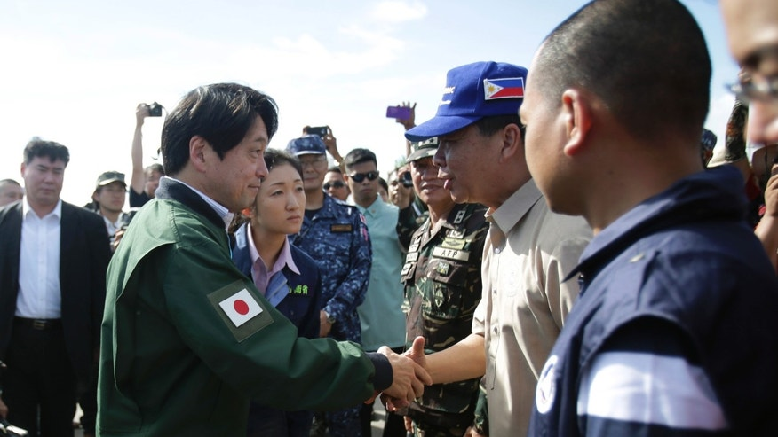 Japanese Defense Minister Itsunori Onodera, left, is welcomed by a Philippine civil defense official as he arrives at the airport in Tacloban, central Philippines on Sunday, Dec. 8, 2013. Onodera went to typhoon-ravaged Tacloban to look at the magnitude of the disaster for additional Japanese aid. (AP Photo/Aaron Favila)