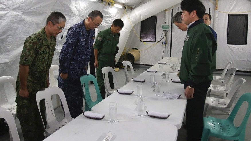 Japanese officers bow to Defense Minister Itsunori Onodera, right, during his visit at their tent in Tacloban, central Philippines on Sunday, Dec. 8, 2013. Onodera went to typhoon-ravaged Tacloban to look at the magnitude of the disaster for additional Japanese aid. (AP Photo/Aaron Favila)