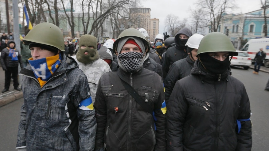 Pro-European Union activists  in military helmets march along streets to block government offices in Kiev, Ukraine, Sunday, Dec. 8, 2013. The third week of protests continue Sunday with an estimated 200,000 Ukrainians occupying central Kiev to denounce President Viktor Yanukovych's decision to turn away from Europe and align this ex-Soviet republic with Russia. (AP Photo/Efrem Lukatsky)