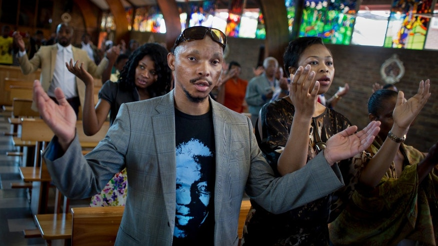 "Mourners attend an early morning church service in memory of Nelson Mandela at the Regina Mundi church, which became one of the focal points of the anti-apartheid struggle, in Soweto, Johannesburg, People in South Africa are taking part in a day of ""prayer and reflection"" for late President Nelson Mandela.  (AP Photo/Ben Curtis)"