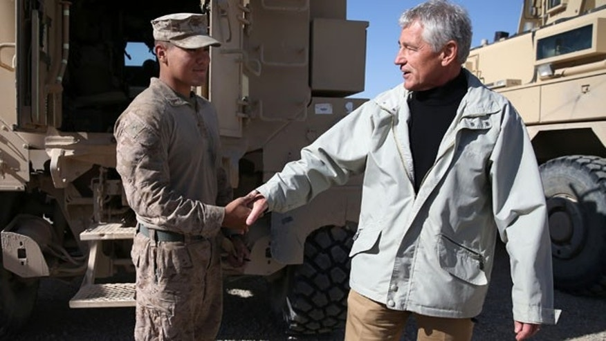December 8, 2013: U.S. Secretary of Defense Chuck Hagel, right, shakes hands with U.S. Marine Lance Cpl. Arron Corona as he works on a MRAP vehicle, at Camp Bastion, Afghanistan. Hagel spoke with troops and thanked them for being deployed for the holidays. (AP Photo/Mark Wilson, Pool)