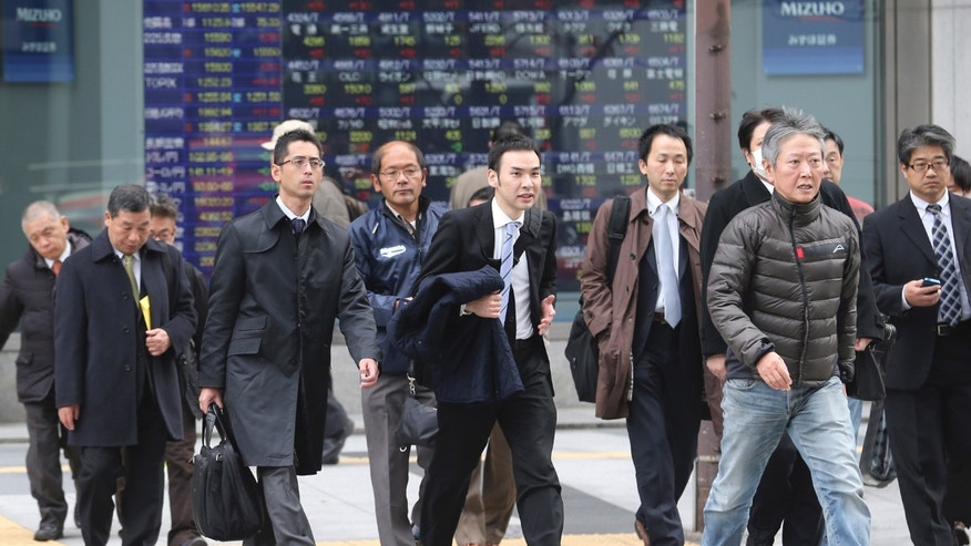 People walk by an electronic stock board of a securities firm in Tokyo, Monday, Dec. 9, 2013. Japan has revised its economic growth estimate for the last quarter downward after finding that capital investment slowed more than expected in July-September. (AP Photo/Koji Sasahara)