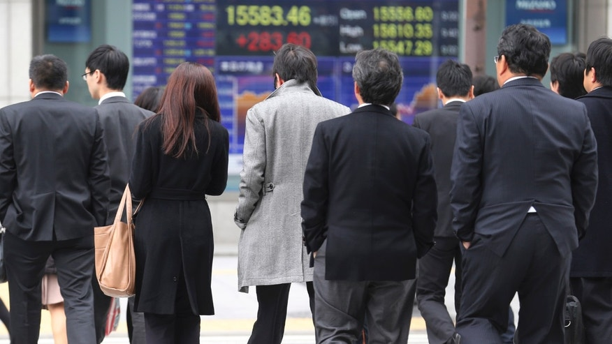 People walk by an electronic stock board of a securities firm in Tokyo Monday, Dec. 9, 2013. Japan has revised its economic growth estimate for the last quarter downward after finding that capital investment slowed more than expected in July-September. (AP Photo/Koji Sasahara)