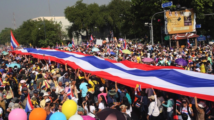 "Anti-government protesters carry a huge Thai national flag as they march to the government house in Bangkok, Thailand Monday, Dec. 9, 2013. Thai Prime Minister Yingluck Shinawatra announced Monday she will dissolve the lower house of Parliament and call elections in an attempt to calm the country's deepening political crisis. The surprise move came as 100,000 protesters vowing to overthrow her government marched through the streets of Bangkok for a ""final showdown."" (AP Photo/Sakchai lalit)"