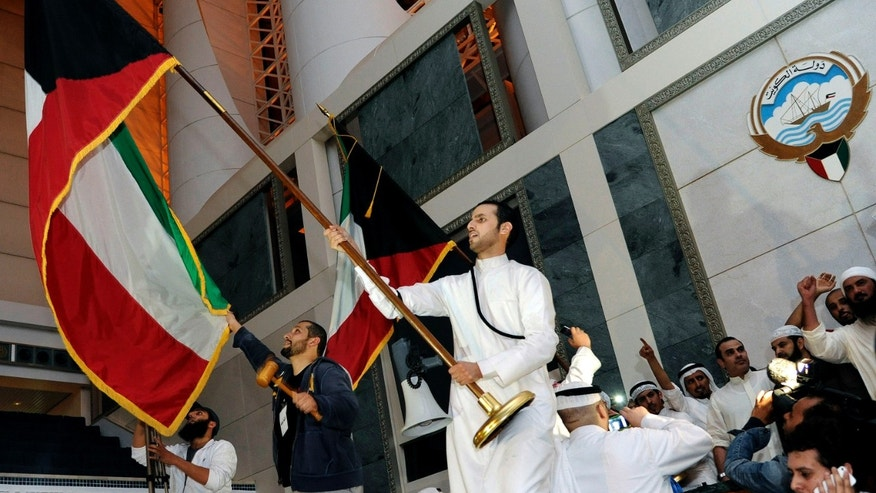 FILE - In this Wednesday, Nov. 16, 2011 file photo, Kuwaiti men wave flags after storming Kuwait's parliament building as hundreds of others protest outside the building, in Kuwait City. A lawyer defending 70 Kuwaiti opposition members on trial in connection with the 2011 storming of the oil-rich Gulf nation's parliament says they have been found not guilty. (AP Photo/Nasser Waggi, File)
