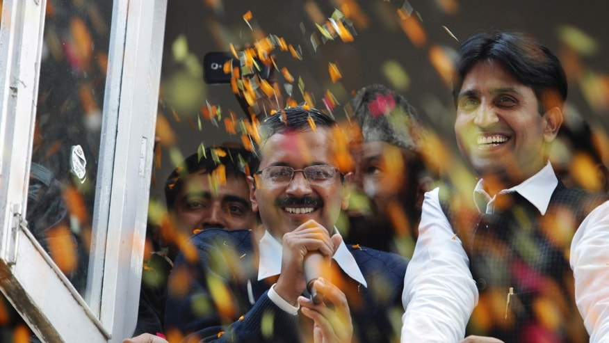Supporters throw flower petals as Arvind Kejriwal, center, leader of India's Aam Aadmi Party, or Common Man's Party, speaks as they celebrate the party's performance in Delhi state Assembly elections, in New Delhi, India, Sunday, Dec. 8, 2013. The new political party played spoiler in the race and pushed Congress into third place, according to early results. The group, led by former tax official hopes next to campaign nationally. (AP Photo/Tsering Topgyal)