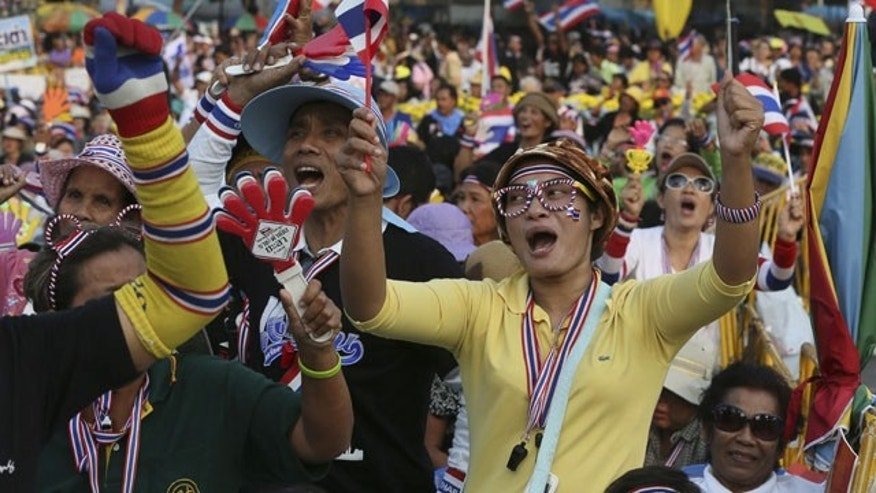 December 8, 2013: Anti-government protesters shout slogans at the Democracy Monument in Bangkok, Thailand. (AP Photo)