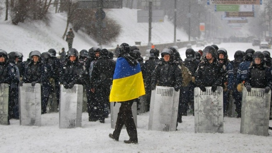 Dec. 9, 2013: A man wearing Ukrainian national flag walks past Ukrainian riot police as they block the road next to Pro-European Union activists gathered on the Independence Square in Kiev, Ukraine. The policemen, wearing helmets and holding shields, formed a chain across Kiev's main street outside the city building. Organizers called on protesters to vacate the city hall and the other building which the opposition had used as its headquarters.
