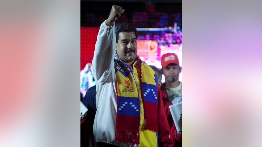 Venezuela's President Nicolas Maduro, gestures as he celebrates with supporters at Bolivar square in Caracas, Venezuela, Sunday, Dec. 8, 2013. Pro-government candidates and opponents of President Nicolas Maduro split Venezuela's disputed mayoral elections Sunday, prolonging a political stalemate in the face of mounting economic problems. (AP Photo/Alejandro Cegarra)