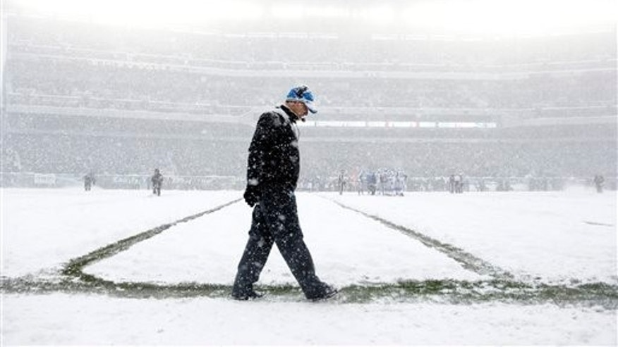 Detroit Lions head coach Jim Schwartz walks the sidelines as snow falls during the first half of an NFL football game against the Philadelphia Eagles, Sunday, Dec. 8, 2013, in Philadelphia. (AP Photo/Matt Rourke)