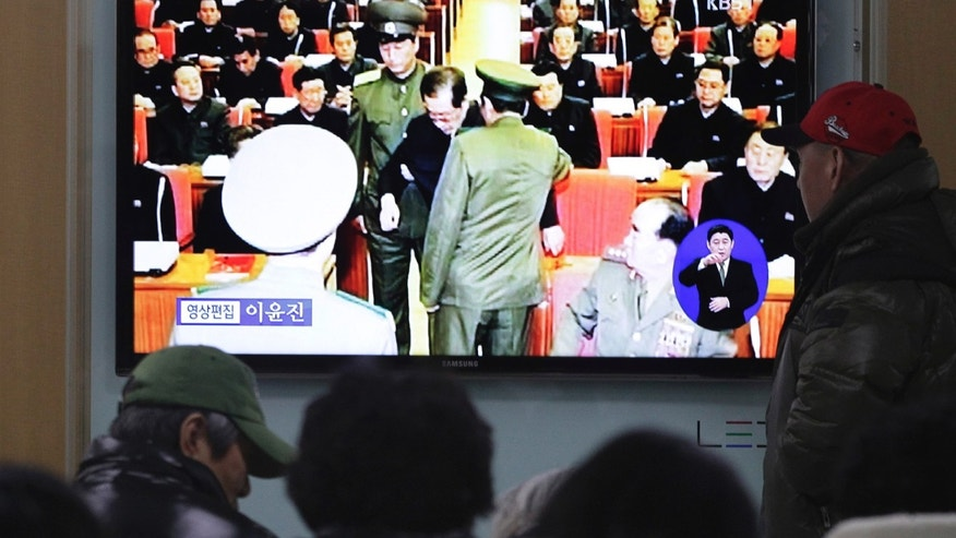 "People watch a TV news program at Seoul Railway Station, South Korea, Monday, Dec. 9, 2013 showing Jang Song Thaek, center, uncle of North Korean leader Kim Jong Un, being grabbed during an emergency meeting of Workers Party's Central Committee in Pyongyang the day before. North Korea announced Monday it had sacked leader Jang, long considered the country's No. 2 power, saying corruption, drug use, gambling, womanizing and generally leading a ""dissolute and depraved life"" had caused Pyongyang's highest-profile fall from grace since Kim took power two years ago. (AP Photo/Ahn Young-joon)"