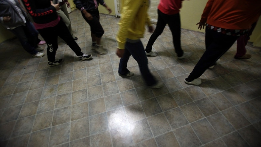 In this Thursday, Sept. 12, 2013 photo, unidentified female inmates walk through a corridor in Serbia's only women's prison in Pozarevac, 60 kilometers east of Belgrade, Serbia. Serbia is in the grips of a crisis of domestic violence that experts say is being fed by chronic poverty, the trauma of wartime atrocities and a culture where brutality against women is traditionally hushed up. (AP Photo/Darko Vojinovic)
