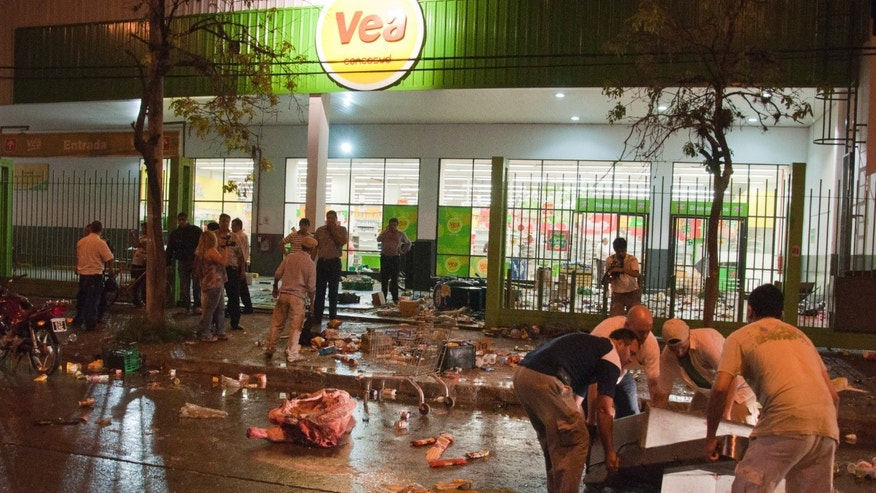 Employees of a supermarket try to recover items left behind by looters after the store was looted in San Miguel de Tucuman, Argentina, Monday. Dec. 9, 2013, Outbreaks of looting have spread across Argentina as mobs take advantage of strikes by police demanding pay raises to match inflation. The central government has dispatched federal police to trouble spots and appealed for an end to what some officials are calling treason. (AP Photo/Bruno Cerimele)