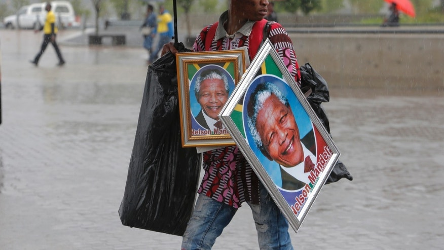 A man sells portraits of Nelson Mandela outside of the memorial service for former South African president Nelson Mandela at the FNB Stadium in Soweto, near Johannesburg, South Africa, Tuesday Dec. 10, 2013. (AP Photo/Tsvangirayi Mukwazhi)