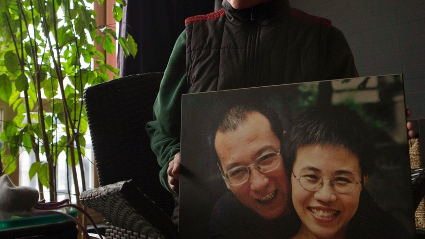 FILE - In this Dec. 6, 2012 file photo, Liu Xia, the wife of China's jailed Nobel Peace Prize laureate Liu Xiaobo, poses with a photo of her and her husband during an interview at her home in Beijing. Five years after his detention, the U.S. is calling for the release of Chinese Nobel Peace Prize winner Liu Xiaobo and an end to his wife's undeclared house arrest. Washington remains deeply concerned about the couple's treatment, along with that of other jailed government critics, Secretary of State John Kerry said in a statement issued Monday, Dec. 9, 2013 in Washington. (AP Photo/Ng Han Guan, File)