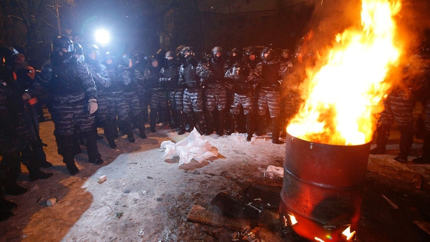 Riot police block an opposition tent camp while displacing pro-European Union activists from their barricades at the Ukrainian presidential administration building in Kiev, Ukraine, Tuesday, Dec. 10, 2013. Heavily armed riot troops broke into the offices of a top Ukrainian opposition party in Kiev and seized its servers Monday, the party said, as anti-government protests crippled the capital for yet another day. Elsewhere police dismantled or blocked off several small protest tent camps set up near key national government buildings in the city. (AP Photo/Alexander Zemlianichenko)