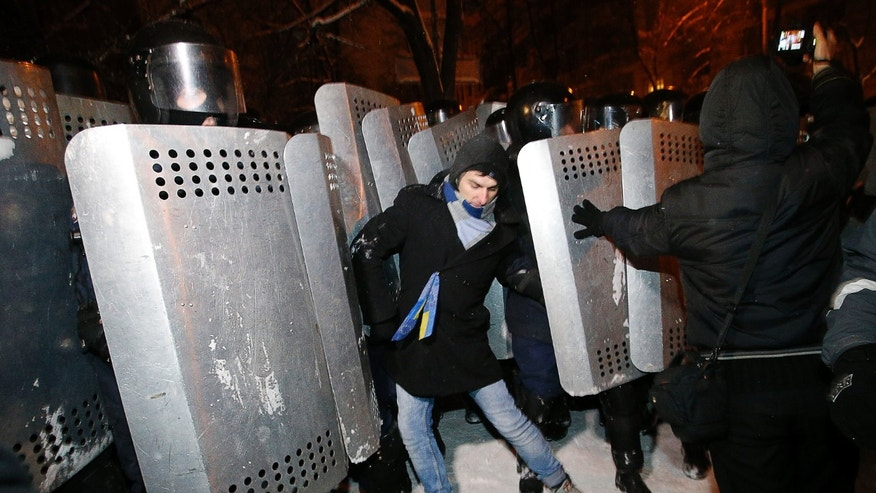 Riot police try to displace pro-European Union activists from their barricades at the Ukrainian presidential administration building in Kiev, Ukraine, Tuesday, Dec. 10, 2013. Heavily armed riot troops broke into the offices of a top Ukrainian opposition party in Kiev and seized its servers Monday, the party said, as anti-government protests crippled the capital for yet another day. Elsewhere police dismantled or blocked off several small protest tent camps set up near key national government buildings in the city. (AP Photo/Alexander Zemlianichenko)