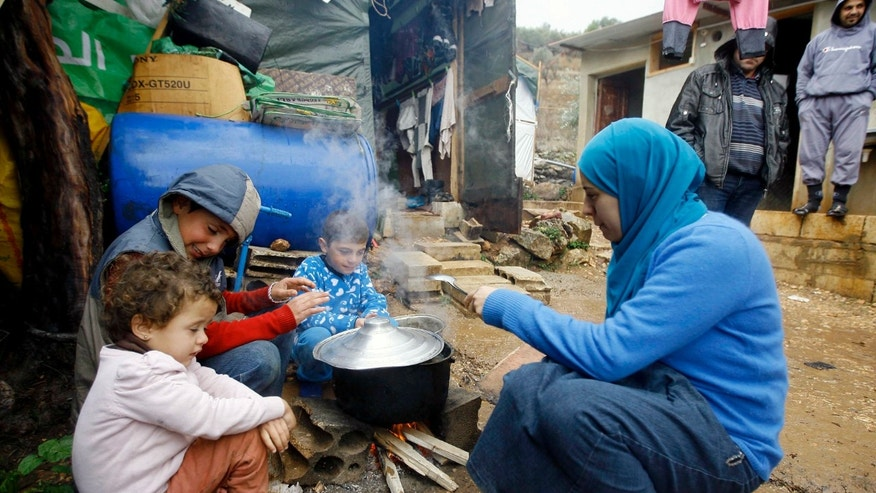 "A Syrian refugee woman with her children prepares food near her tent as a heavy snowstorm batters the region, in a camp for Syrians who fled their country's civil war, in the Chouf mountain town of Ketermaya, Lebanon, Wednesday, Dec. 11, 2013. The United Nations refugee agency says it is ""extremely concerned"" for hundreds of thousands of Syrian refugees scattered across the region amid a snowstorm with high winds and torrential rains. (AP Photo/Mohammed Zaatari)"