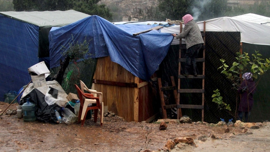 "A Syrian refugee man covers his tent with a tarp as a heavy snowstorm batters the region, in a camp for Syrians who fled their country's civil war, in the Chouf mountain town of Ketermaya, Lebanon, Wednesday, Dec. 11, 2013. The United Nations refugee agency says it is ""extremely concerned"" for hundreds of thousands of Syrian refugees scattered across the region amid a snowstorm with high winds and torrential rains. (AP Photo/Mohammed Zaatari)"