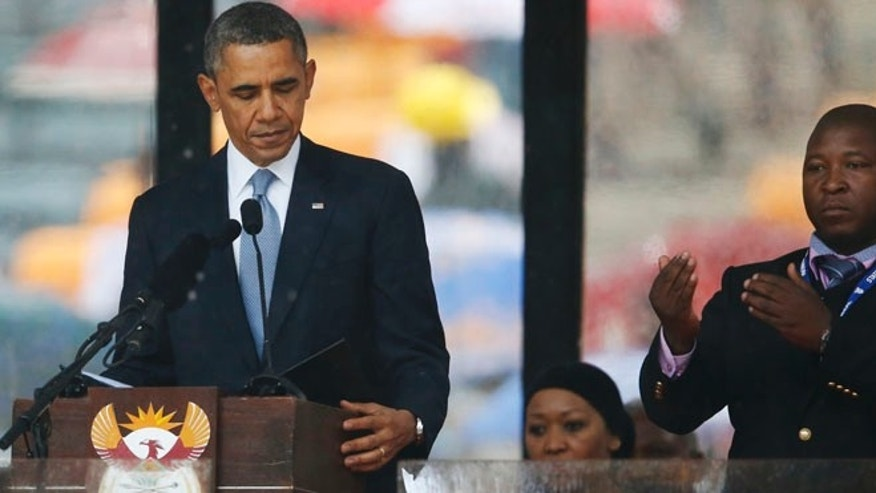 "Dec. 10, 2013: President Barack Obama looks down as he stands next to the sign language interpreter as he makes his speech at the memorial service for former South African president Nelson Mandela at the FNB Stadium in Soweto near Johannesburg.  South Africa's deaf federation said on Wednesday that the interpreter on stage for Mandela memorial was a ""fake."" (AP)"