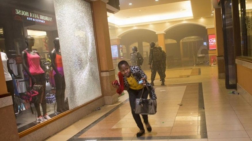 September 21, 2013: A woman who had been hiding during the gun battle runs for cover after armed police enter the Westgate Mall in Nairobi, Kenya, after gunmen threw grenades and opened fire Sept. 21, 2013. (AP Photo/Jonathan Kalan, File)