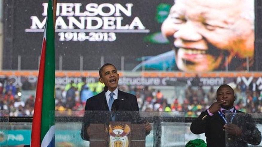 President Barack Obama delivers his speech next to a sign language interpreter during a memorial service at FNB Stadium in honor of Nelson Mandela on Tuesday, Dec. 10, 2013 in Soweto, near Johannesburg.