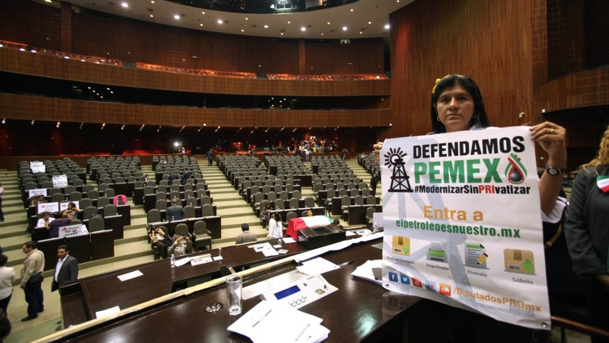 An opposition lawmaker holds a sign in protest against the newly approved energy reform bill in Mexico City, Wednesday, Dec. 11, 2013.