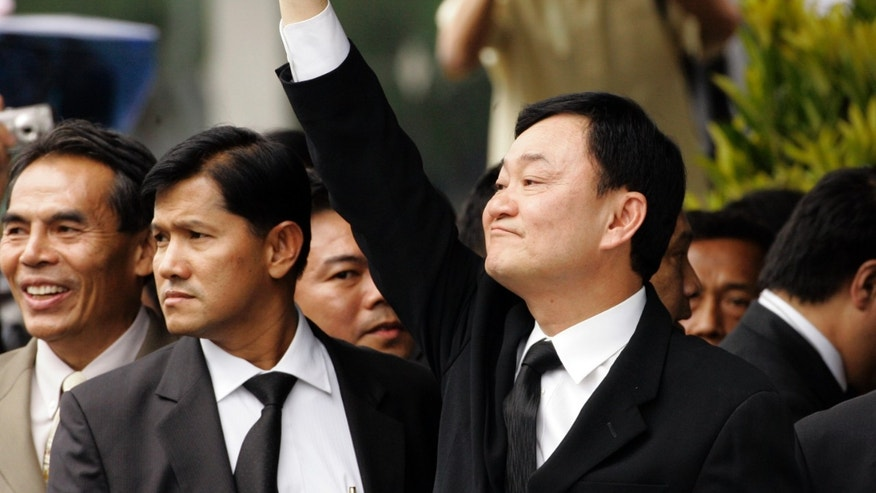 "FILE - In this Thursday, Feb. 28, 2008 file photo, deposed Thai Prime Minister Thaksin Shinawatra, right,  greets supporters on his arrival at Suvarnabhumi airport in Bangkok. The self-exiled, globe-trotting Thaksin, based in a luxurious mansion in Dubai, has remained largely silent during the crisis. In a recent post on his Facebook page, Thaksin denied often-repeated claims that he has been disloyal to the royal family, headed by much-revered but ailing King Bhumibol Adulyadej. ""Thai politics is played out with cruelty and in cold blood. Please don't be cruel to me,"" Thaksin wrote. (AP Photo/David Longstreath, File)"