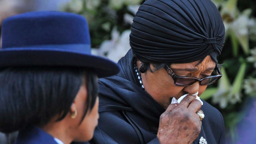 Winnie Madikizela-Mandela, Nelson Mandela's former wife, walks away after paying her respect to former South African President Nelson Mandela during the lying in state at the Union Buildings in Pretoria, South Africa, Wednesday, Dec. 11, 2013.  The woman on the right is unidentified. (AP Photo/Jacoline Prinsloo, Pool)