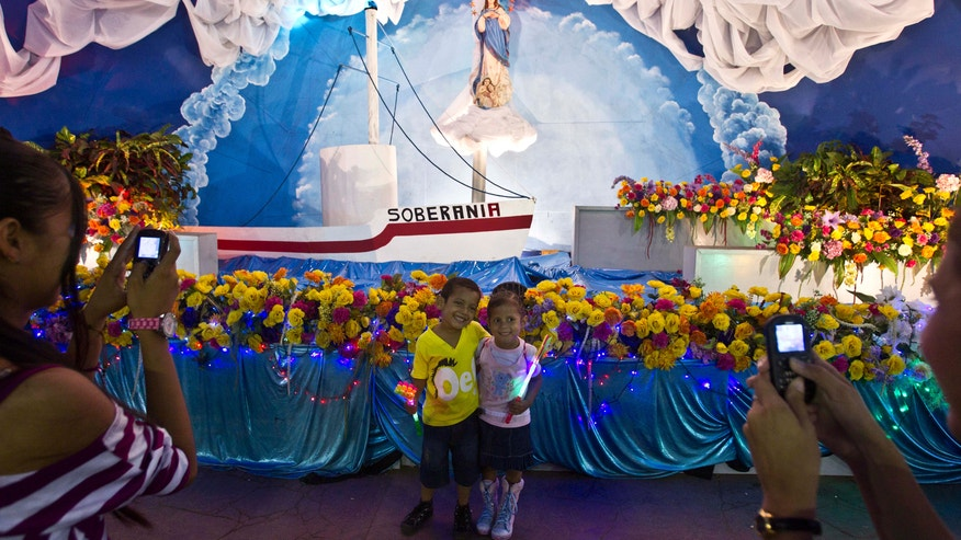 In this Dec. 4, 2013 photo, two children pose for photos in front an altar sponsored by the government of Nicaragua in honor of the Virgin Mary of the Immaculate Conception and the planned Inter-Oceanic Canal in Managua, Six months after the Sandinista government granted a Chinese businessman a 100-year concession to build a vast canal across the country, Nicaraguans are confident the $40 billion canal will become reality, lifting their country from poverty to prosperity. (AP Photo/Esteban Felix)