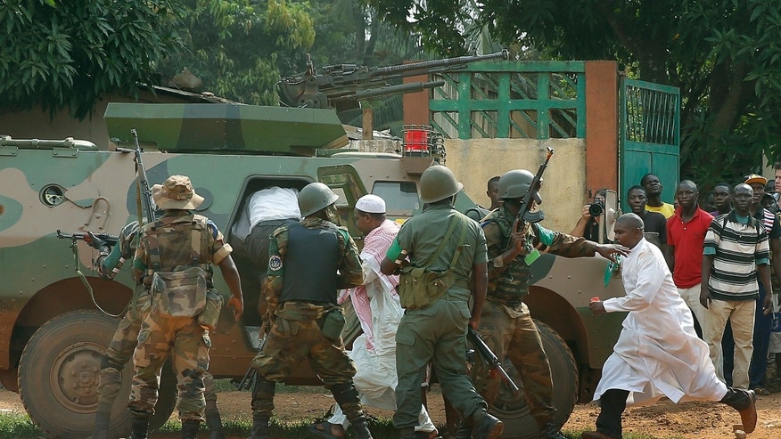 FOMAC troops , regional peacekeepers, evacuate Muslim clerics under a hail of fire from the St Jacques Church in Bangui, Central African Republic, Thursday Dec. 12, 2013. An angry crowd had gathered outside the church following rumors that a Seleka general was inside.  More than 500 people have been killed over the past week in sectarian fighting in Central African Republic. (AP Photo/Jerome Delay)