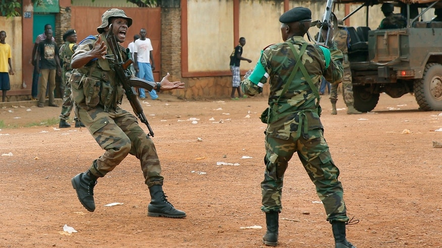 A FOMAC  regional peacekeeper screams for a cease fire as troops fire their guns to secure the evacuation of  Muslim clerics from the St Jacques Church in Bangui, Central African Republic, Thursday Dec. 12, 2013. An angry crowd had gathered outside the church following rumors that a Seleka general was inside.  More than 500 people have been killed over the past week in sectarian fighting in Central African Republic. (AP Photo/Jerome Delay)