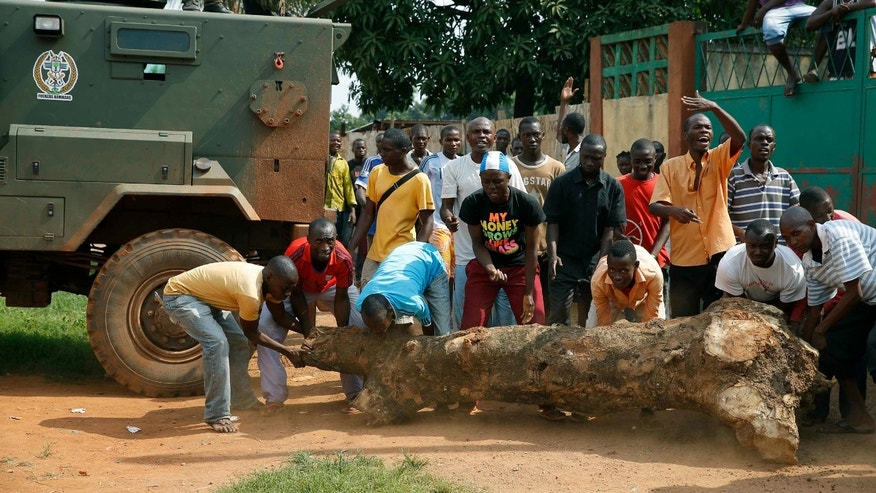 Angry crowd move a tree trunk to try to prevent FOMAC troops, regional peacekeepers, from evacating Muslim clerics from the St Jacques Church in Bangui, Central African Republic, Thursday Dec. 12, 2013. An angry crowd had gathered outside the church following rumors that a Seleka general was inside.  More than 500 people have been killed over the past week in sectarian fighting in Central African Republic. (AP Photo/Jerome Delay)