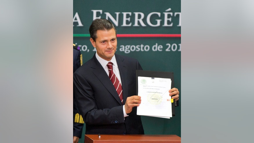 FILE - In this Aug. 12, 2013 file photo, Mexico's President Enrique Pena Nieto shows to the audience his proposal that would allow private firms to participate in the oil industry in Mexico City. The opening of Mexico's oil industry to private and foreign investment caps a remarkable series of legislative victories by President Pena Nieto, who is trying to re-engineer the country's most dysfunctional institutions. (AP Photo/Eduardo Verdugo, File)
