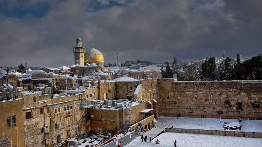 Western Wall and the Dome of the Rock, some of the holiest sites for for Jews and Muslims, are covered in snow in Jerusalem, Friday, Dec. 13, 2013. Early snow has surprised many Israelis and Palestinians as a blustery storm, dubbed Alexa, brought gusty winds, torrential rains and heavy snowfall to parts of the Middle East. (AP Photo/Dusan Vranic)