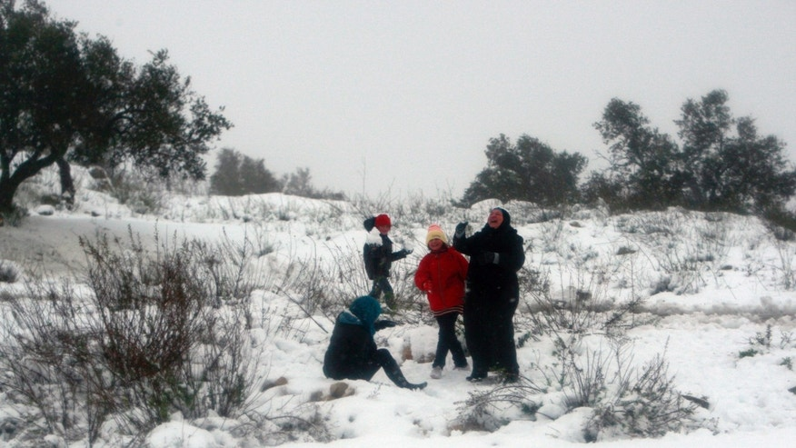 Palestinians play with the snow in the West Bank village of Seelat Al-Daher near Jenin city, Friday, Dec. 13, 2013. Early snow has surprised many Israelis and Palestinians as a blustery storm, dubbed Alexa, brought gusty winds, torrential rains and heavy snowfall to parts of the Middle East. (AP Photo/Mohammed Ballas)