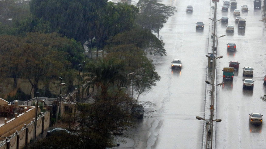 Vehicles travel in the rain in Cairo, Egypt, Friday, Dec. 13, 2013. A blustery storm, dubbed Alexa, battered parts of the Middle East. Cairo's temperature has also dropped down to six degrees Celsius (43 in Fahrenheit) in the morning. (AP Photo/Amr Nabil)