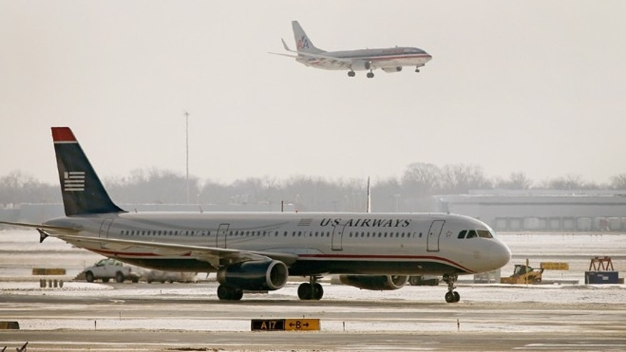 CHICAGO, IL - DECEMBER 09:  An American Airlines jet flies over a US Airways jet at O'Hare Airport on December 9, 2013 in Chicago, Illinois.  American Airlines announced today that it had completed a merger deal with US Airways. The deal will make American Airlines the world's largest airline, flying about 6,700 flights per day.  (Photo by Scott Olson/Getty Images)