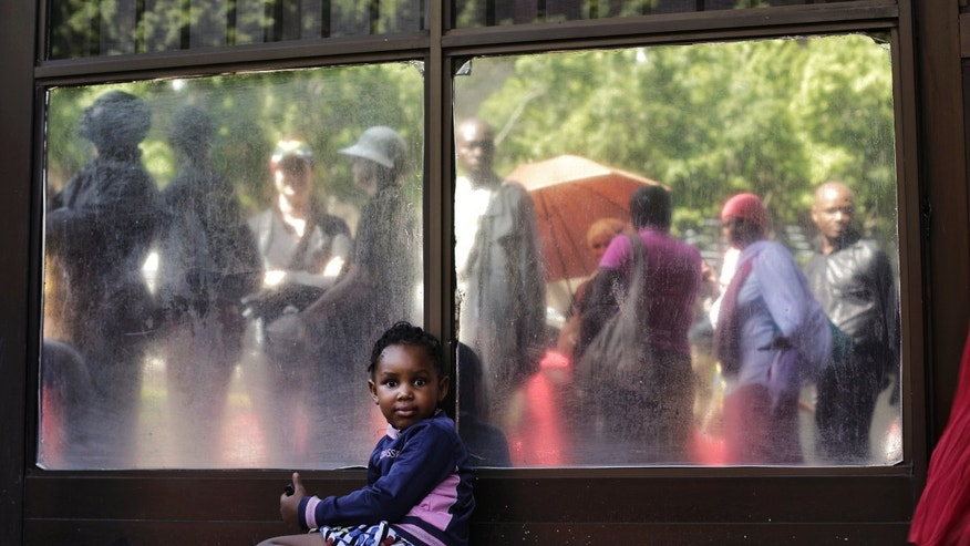 Four year old girl Queen rests in the shade from waiting in line, seen in the reflection, with thousands  of other people to pay respect to South Africa President Nelson Mandela laying in state the third and final day at the Union Buildings in Pretoria, South Africa, Friday, Dec. 13, 2013. (AP Photo/Markus Schreiber)