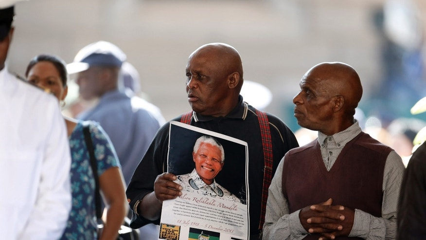 A man holding an image of former South African President Nelson Mandela pays his respects as he passes Mandela's casket, on the third and final day of lying in state at the Union Buildings in Pretoria, South Africa, Friday, Dec. 13, 2013. (AP Photo/Matt Dunham, Pool)