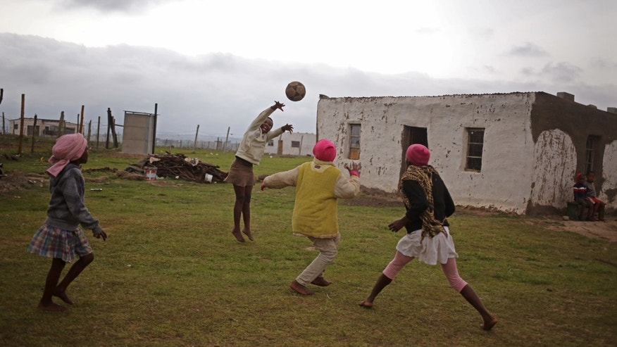 Children play with a ball near the home of former president Nelson Mandela in Qunu, South Africa, Sunday, Dec. 8, 2013. The home  where Nelson Mandela grew up had mud walls, a grass roof, and a floor polished smooth with cow dung. That was in the 1920s. When people flood Mandela's village on Sunday for the former president's burial, they will be in a place that _ except for a gleaming new highway and a strong cellphone network lags decades behind the  developed world. (AP Photo/Schalk van Zuydam)